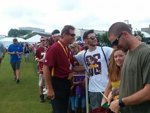 Robert Sipos taking a picture with one of the Redskins all-time great Quarterback, Joe Theismann
